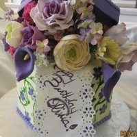Olivia 1 1/2 tier, handpainted fondant finish, with flowers, bow, and lid handmade of sugarpaste. Roses, ranunculus, calla lilies, hydrangeas,...
