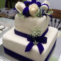 Navy Blue Cake 2 tier square with navy blue ribbon and bows and fresh flowers