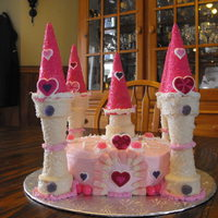Princess Castle Cake normal round cake with butter vream icing and the towers are made with ice cream cones dipped in melted chocolate and rolled in crystal...