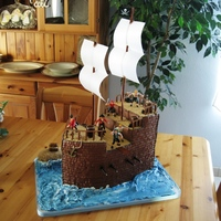 Pirate Ship Chocolate cake carved into a pirate ship, covered in chocolate buttercream. The decks are chocolate candy melts. Ship railings, barrels,...