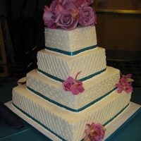 4-Tier Buttercream Wedding Cake Buttercream cake with buttercream piping, satin ribbon and fresh flowers