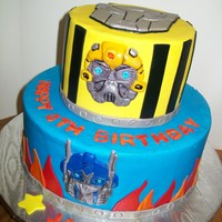 Transformers 6 and 10 inch tiers iced in buttercream with fondant accents.