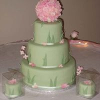 In Bloom Fondant covered cake with silk flower ball on top. 2 matching mini cakes on each side.