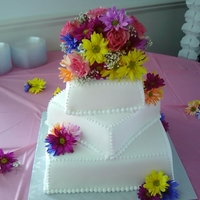 Square Wedding Cake french vanilla cake with strawberry filling and buttercream frosting. Fresh flowers arranged and top and surrounding.