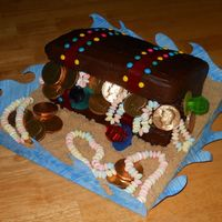Buried Treasure Treasure chest cake. White cake with chocolate frosting. Gold covered chocolate coins, ring pops and candy necklaces. The sand is light...