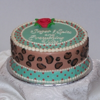 Leopard Baby Shower This cake was designed to match the invitations. The cake is iced in buttercream with a fondant ribbon rose on top.