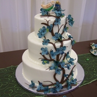 Branch Wedding Cake The cake is iced in buttercream. The branch is chocolate buttercream. The bride provided silk flowers to match all of her decorations.