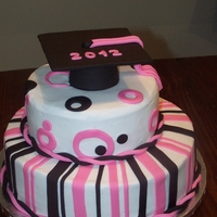 "Pink And Black Grad Cake Buttercream iced with fondant strips and circles. Fondant graduation cap on top. 12"" and 8"" round cakes"