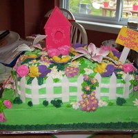 Garden Cake 1/2 sheet with 1/4 sheet. Iced in buttercream, fondant fence, flowers. buttercream flowers and leaves.