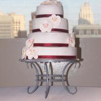 Orchid Wedding Cake 4 Tiered round wedding cake with gumpaste orchids and wine colored ribbon.