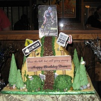 "Dave's Mountain Bike Over The Hill Cake 4/8/11 Cake was 9"" pyramid chocolate fudge cake with 9"" square base. Icing is buttercream icing. All decorations are edible:..."