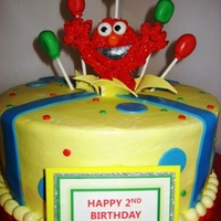 "Silly Elmo 10"" French Vanilla with raspberry mousse filling iced in all b/c with fondant decor. Elmo is fondant iced in royal."