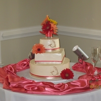 Ivory Wedding Cake real gerber daisies accent this cake.