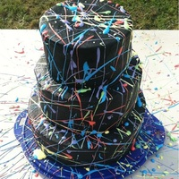 Splatter Paint Cake Black crusted buttercream icing with royal icing splatter paint.Wow so much fun to make! With multicolored layers:bottom tier was white...