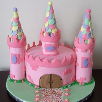 "Princess Castle   8"" Red velvet cake, cream cheese frosting, turrets are RKT, roof peaks are ice cream cones."