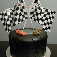Cars Tire Cake Fondant covered Chocolate Cake with Chocolate buttercream, plastic racing flags and cars