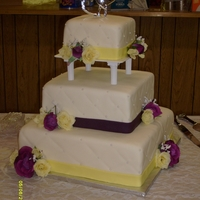 Quilted Sq Wedding Cake White cake with buttercream covered in MMF. Edible pearls and silk flowers...yellow and purple. Top Tier was actually Gluton Free.