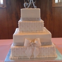 4 Tier Bling With Bow Alternating layers of red velvet and strawberry cake frosted with buttercream. Bow is gumpaste.