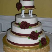 Wedding Cake With Flowers   Cake iced with buttercream, fondant burgundy border, fondant pearls painted with gold shimmerdust. Flowersaand leaves made with fondant.