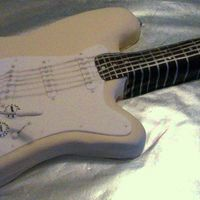 Fender Stratocaster Guitar   Cake covered in fondant with fondant accents.