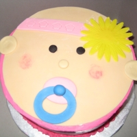 Baby Face With Sunflower Strawberry cake with buttercreme icing. Baby face made of fondantWith sunflower cupcake