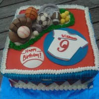 Sports Themed Birthday Cake   Chocolate WASC with candy clay sports equipment, vanilla bc and gp jersey.