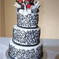 Black And White Scrolls 3 Tier round white cake with black scrolls. Fondant bow, black,white,silver and red. Silver used on bow was sprayed on with an airbrush,...