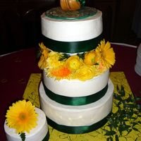 Romantic Garden Celebration 10 inch on top of a 12 inch, 8 inch is floating on fresh flowers. 6 inch on the side. All cakes decorated with green satin ribbon. Topper...