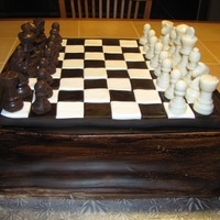 Chess Game Chess game cake covered in fondant, chess pieces are molded chocolate. The cake is vanilla cake, half of it tinted brown for checkerboard...