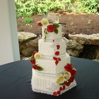 Val's Wedding Cake  Four tier hexagon with a different white on white for each layer. Sugar paste Calla Lilies and Red Roses. Outdoor wedding with temps in...
