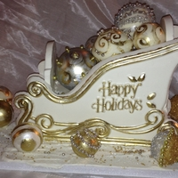 Christmas Sleigh In White Chocolate White Chocolate Christmas Sleigh and Ornaments. Decorated with Gold and Silver Luster High Lighter. Also Gold and Silver Wilton Sugars.