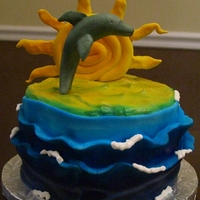 Dolphin Birthday This is a 6 in double layer cake. It's a white cake with vanilla buttercream icing. The dolphin and sun are made from fondant.