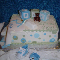 Jessica's Baby Shower Double 9 x 19 cake with buttercream frosting and fondant accents, in blues and greens. Building blicks, chocolate baby bottle with teddy...