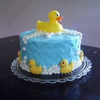 Ducky Birthday Cake WASC cake with buttercream. The duck on top is a new bath ducky, as requested. . the ones around the bottom are candy melts that I poured...