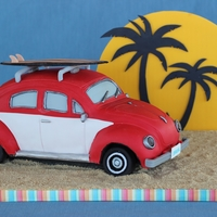 Vintage Vw Bug On Beach With Sunset Backdrop  This is a vintage VW Bug cake, sculpted and covered in fondant. The surfboard is made from gumpaste. The sunset backdrop is a cake board...