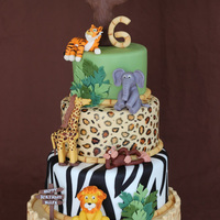 Safari Themed Jungle Birthday Cake  This is a birthday cake I made for my niece's safari themed party. The tree, sign and animals were all made from modeling chocolate....