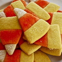Candy Corn Cookies  My sister and I made these cookies together, which is rare because her cooking needs a lot of practice. I just colored some dough orange...