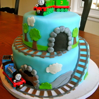 Thomas The Train I made this for my 3 year old cousin who loves trains. all fondant decorations except trains. I bought the train toys online.