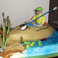 Kayak  Vanilla cake base, chocolate cake kayak with vaniilla butter cream. Guy, lily pads, cat tails and paddles are fondant. Piping gel water....