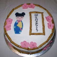 Japanese Kokeshi Doll Cake Tahitian vanilla cake and butter cream icing covered in fondant; fondant decorations; happy birthday written in Japanese romaji characters...