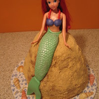 Ariel Yellow cake w/choc pudding, chocolate frosting and pulverized teddy grams as sand. White choc shells, fondant tail, necklace and shell top...
