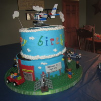 "Lego City 10"" white and 8"" offset chocolate cakes. Lego city theme. fondant accents and lego toys (helicopter, people, cars). Cake board..."