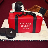 "Oh Puck! 50Th Hockey Bag Cake 9x13 hockey bag covered in fondant with RKT skate, cake pucks, and isomalt ""ice."" Stick is cakeboard covered in fondant. TFL."