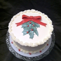 Christmas Holly Cake Dark Red Velvet torted and finished wtih vanilla buttercream. Greenery, bow and berries all vanilla fondant, brushed with pearl dust for a...
