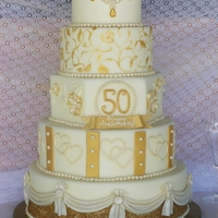 Golden Anniversary Cake This is a cake I made for my parent's 50th Wedding Anniversary. Cake covered in fondant, 2nd tier is hand painted with gold luster...