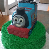 "Thomas The Train 12"" vanilla round topped with a Thomas the Train carved chocolate cake. Thomas's face is made of fondant, everything else is..."