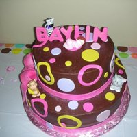 "Baylin's Cake 8"" round on top of 12"" round cake covered in chocolate buttercreame and accented with fondant circles and dots. Bow is made out..."