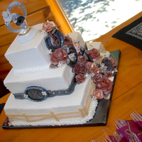 Western Horseshoe Wedding Cake Frosted in buttercream, with buttercream roses, handmade fondant horseshoes, belt and buckle, and buttercream fence. . .custom made to fit...