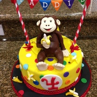 Curious George Birthday Cake Strawberry cake with bc icing, covered in fondant with modeling chocolate monkey, hat & bananas and gumpaste letter flags.