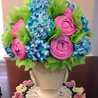 Cupcake Flower Bouquet For Mothers Day Pink roses are orange dream flavored and blue hydrangeas are chocolate fudge flavored, both with buttercream piped flower details.